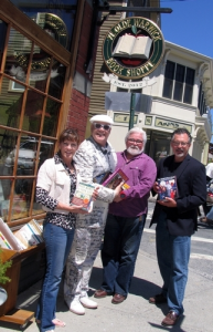 """To help support Literacy Orange's book sale; the merchants are asking people to donate used books and deliver them to Ye Olde Warwick Book Shoppe at 31 Main St. in the Village of Warwick. From left, Literacy Orange Executive Director Christine Rolando, Sidewalk Sale co-chair Tim Mullally, Ye Olde Warwick Book Shoppe owner Thomas Roberts and author and Literacy Orange volunteer Tom Mattingly, holding a copy of his book, """"The Single Father's Guide."""""""