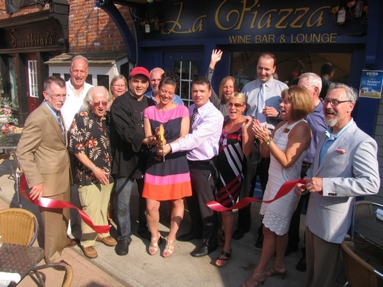 Surrounded by members of the Warwick Valley Chamber of Commerce, friends and business neighbors, owner Tony Sylaj, his wife, Lauren, and partner Nick Ahmetaj cuts the ribbon held by Town of Warwick Supervisor Michael Sweeton (far left) and Mayor Michael Newhard (far right).