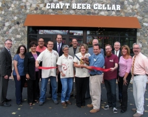 On Thursday, October 2, Town of Warwick Supervisor Michael Sweeton (left), Mayor Michael Newhard (right) and members of the Warwick Valley Chamber of Commerce joined owners Michael and Maggie Keller (center) and their staff for a ribbon cutting ceremony at Craft Beer Cellar.