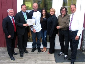 Photo by Roger Gavan County Executive Steve Neuhaus presented Patrick Gonzales with a certificate of recognition for his entrepreneurial spirit.That same day Jim Mezzetti of Myles Financial Services awardded Gonzales with a membership in the Warwick Valley Chamber of Commerce. From left, Jim Mezzetti, Orange County Executive Steve Neuhaus, Moore Dairy owner Patrick Gonzales and General Manager Grazia Iodice, WTBQ Station Manager Taylor Sterling, station owner Frank Truatt and Orange County District Attorney David Hoovler.
