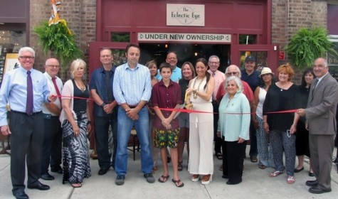 On Friday, Aug. 7, town, village and business representatives joined Walter Welsh and his wife Joanne Magro and their friends and associates for the grand opening of the all-new Eclectic Eye. Warwick Deputy Mayor Barry Cheney (far left) and Town of Warwick Deputy Supervisor James Gerstner (far right) hold the ribbon about to be cut by co-owner Joanne Magro (center) with her husband Walter Welsh and son Bryce Ruvo, 13, joined by members of the Warwick Valley Chamber of Commerce, their friends and associates.