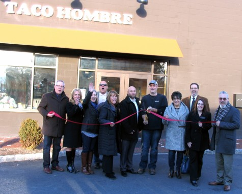 Photo by Roger Gavan On Thursday, Jan. 7, Mayor Michael Newhard (far right), Warwick Valley Chamber of Commerce Executive Director Michael Johndrow (far left) and members of the Chamber's Board of Directors joined co-owners Bo Kennedy and Chad Wieber (center) for a ribbon cutting ceremony to celebrate the fifth anniversary of Taco Hombre Mexican Restaurant.