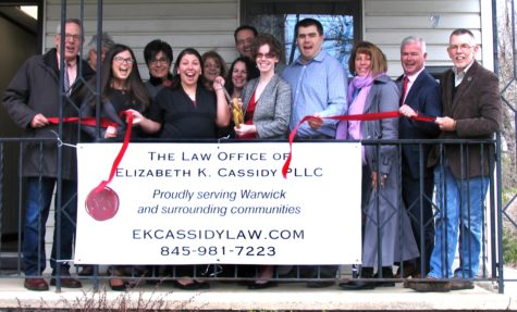 Photo by Roger Gavan On Friday, April 8, Town of Warwick Supervisor Michael Sweeton (far right) and members of the Warwick Valley Chamber of Commerce joined Cassidy (cutting ribbon center right), her husband, Jeremy Cook, and her associate attorney, Jessica Mahoney, for the grand opening of her new office.