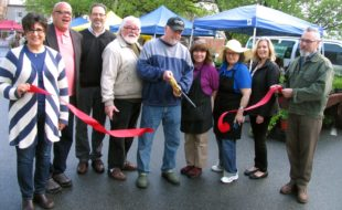 Photo by Roger Gavan It rained, heavily at times, on Sunday morning, May 8. But at 9:30 a.m. the sun shone just in time for a ribbon-cutting ceremony to celebrate the official opening of the 23rd season of the Warwick Farmers Market. From left, Warwick Valley Chamber of Commerce past president Sherry Bukovcan, board members Wayne Paterson and Garrett Durland, Merchant Guild President Tom Roberts, Farmers Market Chair Jack Hillery, Farmers Market Steering Committee member Annette Sanchez, Market Manager Penny Steyer, chamber board member Kim Starks and Mayor Michael Newhard.