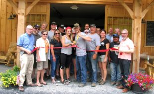 """Photo by Roger Gavan On Saturday, June 4, public officials and representatives of the Warwick Valley Chamber of Commerce joined members of the Pennings family, friends and staff to celebrate the grand opening of the Pennings Farm Cidery. Tori and Steve """"SJ"""" Pennings Jr., (center) alongside their parents Steve and Jill Pennings, cut the ribbon held by Town of Warwick Supervisor Michael Sweeton (far left) and Mayor Michael Newhard (far right)."""