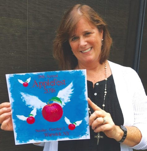 Terri Davis holds her award-winning design that will be featured on Applefest 2016 T-shirts.