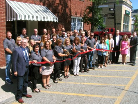 Photo by Roger Gavan On Aug. 4, Town of Warwick Supervisor Michael Sweeton (far right) and members of the Warwick Valley Chamber of Commerce joined the company's General Manager Marie Corlett and Product Manager Jean Beattie (center) along with other employees of the firm to celebrate the return to its original name, Warwick Valley Telephone, with a ribbon-cutting ceremony.